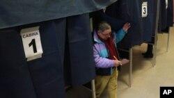 Seorang warga keluar dari bilik suara setelah mengikuti pemilihan umum di salah satu TPS di Milan, Italia (24/2).