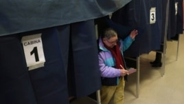 A man exits a polling booth after casting his ballot in Milan, Italy, February 24, 2013.
