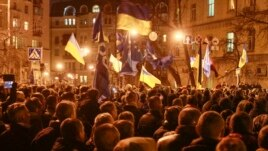 People sing the national anthem as they attend a rally held by supporters of EU integration near the presidential administration building in Kyiv Dec. 3, 2013.