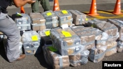 FILE - Costa Rican police officers guard about two tons of cocaine in this handout photo provided by Costa Rica's Ministry of Public Security, Feb. 1, 2012. A cocaine-smuggling operation at the international airport in San Juan, Puerto Rico, has led to 12 suspects being indicted.