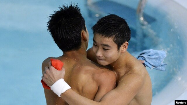 China's Cao Yuan (R) hugs his team mate Zhang Yanquan after their last dive in the men's synchronized 10m platform final during the London 2012 Olympic Games at the Aquatics Centre July 30, 2012.