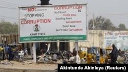 Un homme circule en moto près d'un panneau de campagne contre la corruption le long d'une route dans le district de Dangi dans la ville de Kano au nord du Nigeria, le 19 janvier 2016.