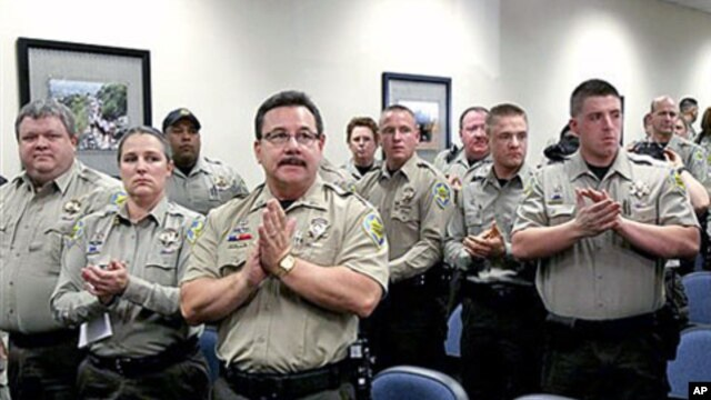 Maricopa County Sheriff's Office jail officers, who lost their federal power to check whether inmates are in the county illegally, give Sheriff Joe Arpaio a standing ovation after they turned in their credentials when federal officials pulled the Sheriff'