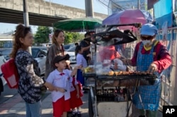 Schoolchildren gather around street vendors outside their school in Bangkok, Thailand, Nov. 1, 2018. A report by the United Nations Food and Agricultural Organization released Friday says some 486 million people are malnourished in Asia and the Pacific, a U.N. report found.