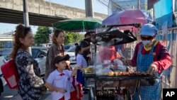 Schoolchildren gather around street vendors outside their school in Bangkok, Thailand, Nov. 1, 2018.