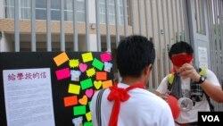 遊行人士在可能推行國民教育的小學門前貼上公開信及網民留言,呼籲學校抗拒洗腦教育