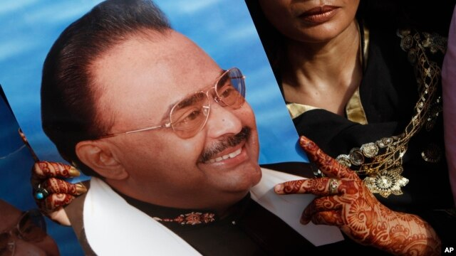 FILE - This is a May 20, 2013  file photo of a supporter of Altaf Hussain, leader of the Muttahida Qaumi Movement, (MQM) holds his picture during a protest rally in Karachi, Pakistan.