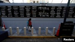 "Pedestrians walk by a sign that reads ""Memory and Justice"" next to the names of the victims of the 1994 AMIA bombing, placed outside the AMIA Jewish community center in Buenos Aires, Argentina, Jan. 21, 2015."