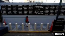 عبور رهگذران از کنار تابلویی برای یادبود قربانیان بمب گذاری ۱۹۹۴ در آرژانتین