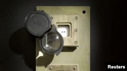Tiga sampel batu bulan, yang menurut Sotheby satu-satunya batu bulan yang terdokumentasi dan berada dalam kepemilikan individu, yang berasal dari misi tidak berawat Soviet Luna-16 pada tahun 1970 yang kembali ke bumi dan diperlihatkan terbungkus dalam kotak berpenutup kaca dengan lensa yang dapat disetel, New York, 15 Oktober 2018 (courtesy: Sotheby via Reuters)
