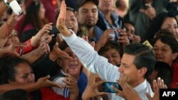 A handout photo released by the Mexican presidency press office shows President Enrique Pena Nieto (R) waving to supporters during the inauguration of the Women's Health City in Cuatitlan Izcalli, Mexico state on Nov. 18, 2014.