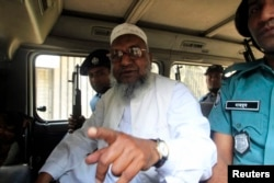FILE - Bangladesh's Jamaat-e-Islami leader Abdul Quader Mollah talks from a police van after a war crimes tribunal sentenced him to life imprisonment in Dhaka.