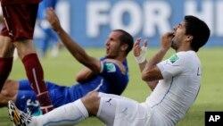 Pemain Uruguay Luis Suarez berakting memegang giginya setelah menggigit pemain Italia Giorgio Chiellini dalam pertandingan di Natal, Brazil (24/6).