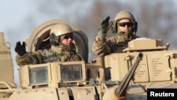 FILE - U.S. soldiers are seen atop a military vehicle deployed in Latvia, in Riga Nov. 18, 2014.