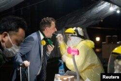 一名抵达上海的澳大利亚旅客正在上海国际机场接受新冠病毒检测。(2020年3月21日)