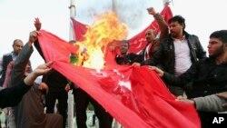 Demonstran membakar bendera Turki dalam sebuah protes menuntut penarikan pasukan Turki dari Irak utara, di Basra, Irak, 18 Desember 2015.