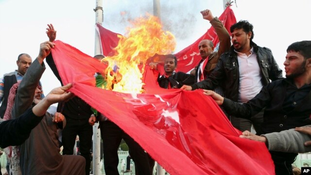Protesters burn a Turkish flag during a demonstration calling for the withdrawal of Turkish troops from northern Iraq, in Basra, Iraq, Dec. 18, 2015.