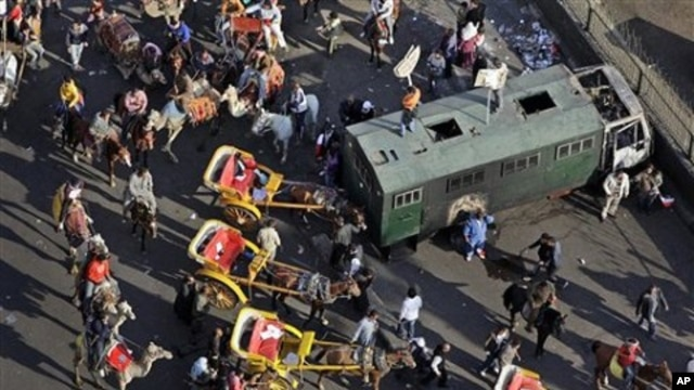 Pro-government demonstrators on horses, camels, and horse-drawn carriages used in the clashes, retreat back past a police truck that was burned in previous clashes a week ago, near Tahrir square in Cairo, Egypt, February 02, 2011.