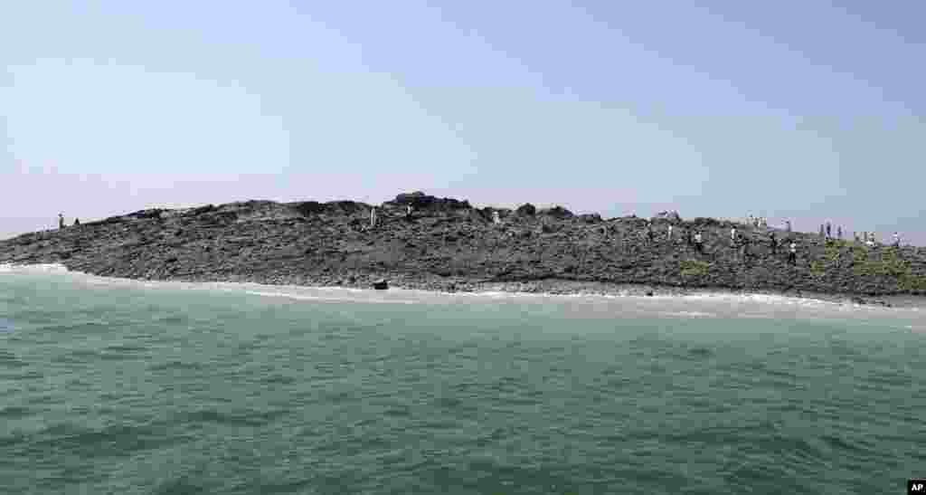 People walk on an island that reportedly emerged off the Gwadar coastline in the Arabian Sea.A deadly magnitude 7.7 earthquake struck in the remote district of Awaran in Pakistan's Baluchistan province with enough force to create a small island visible off the southern coast, Pakistani officials said.