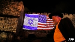 A picture shows a giant US flag screened alongside Israel's national flag by the Jerusalem municipality on the walls of the old city.
