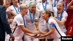 United States forward Abby Wambach (20) and United States defender Christie Rampone (3) hoist the trophy after defeating Japan in the final of the FIFA 2015 Women's World Cup at BC Place Stadium, July 5, 2015.