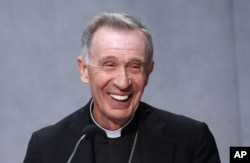 FILE - Monsignor Luis Francisco Ladaria Ferrer smiles during a news conference at the Vatican, Sept. 8, 2015. Pope Francis has tapped Ferrer to lead the powerful congregation that handles sex abuse cases and guarantees Catholic orthodoxy around the world.