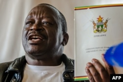 FILE: Zimbabwe National Liberation War Veterans Association (ZNLWVA) Secretary-general Victor Matemadanda holds up the country's constitution at a press conference in Harare on November 15, 2017.