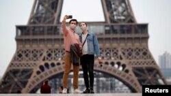 Wisatawan mengenakan masker, berfoto selfie di alun-alun Trocadero dekat Menara Eiffel di Paris, Perancis, 16 Mei 2020. (Foto: dok).