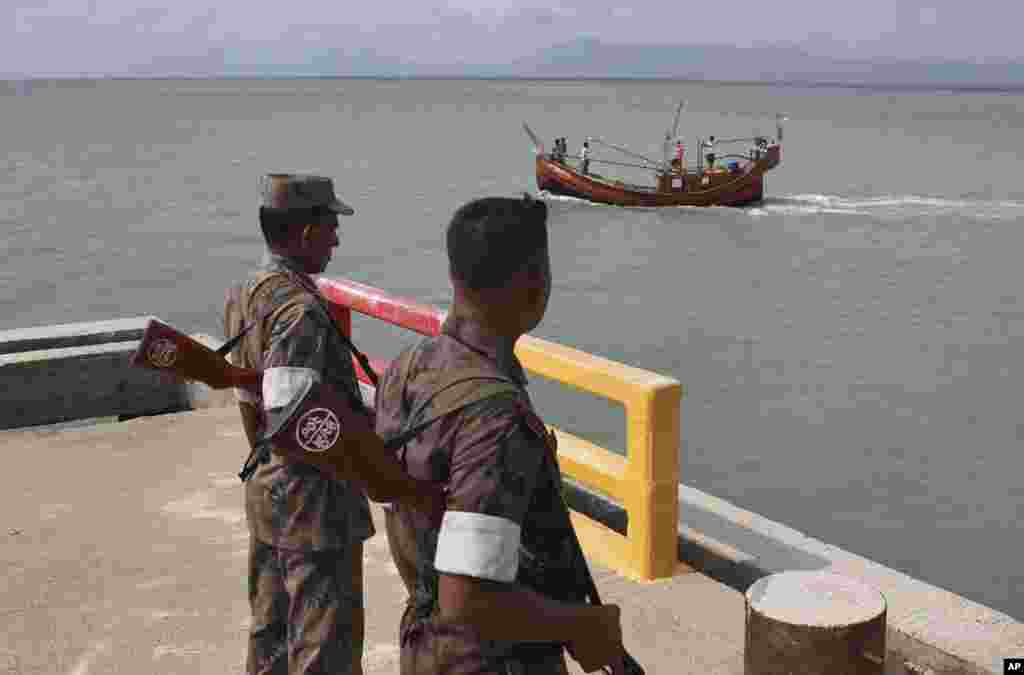 Bangladeshi Border Guard soldiers keep watch at a wharf in Taknaf, Bangladesh, June 12, 2012.