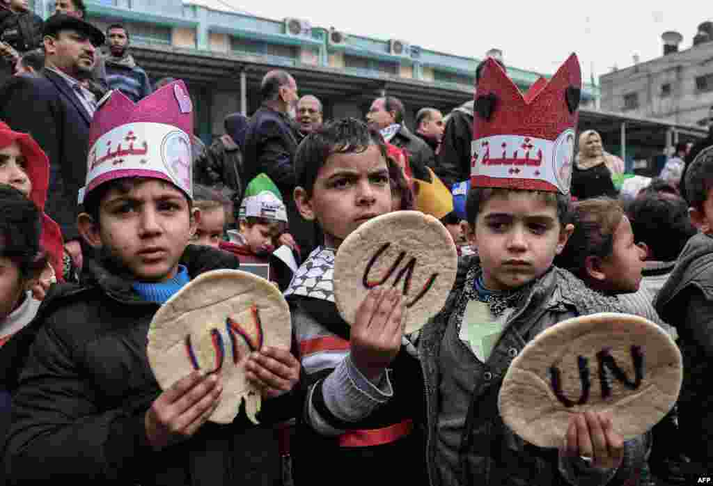 Palestinian children hold bread patties during a protest against aid cuts, outside the United Nations' offices in Khan Yunis in the southern Gaza Strip.