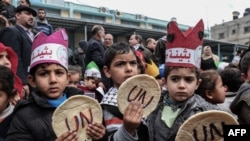 FILE - Palestinian children hold bread patties during a protest against aid cuts, outside the United Nations' offices in Khan Yunis in the southern Gaza Strip on Jan. 28, 2018.