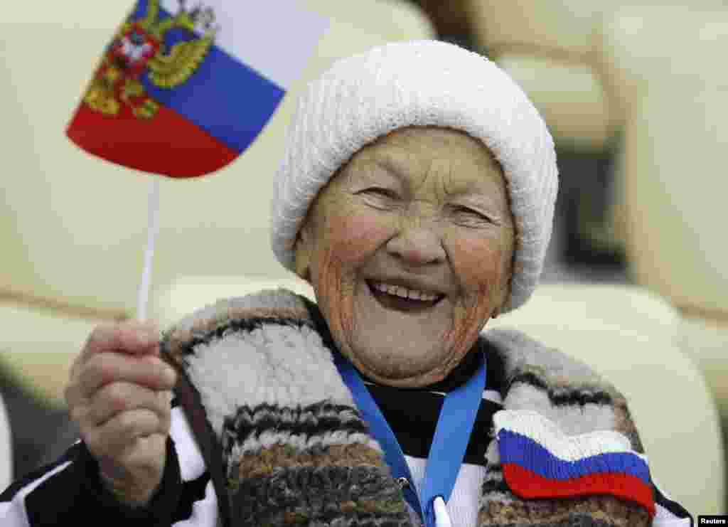 A Russian supporter waves the national flag before the women's 5,000-meter speed skating race at the Adler Arena, Sochi, Feb. 19, 2014.