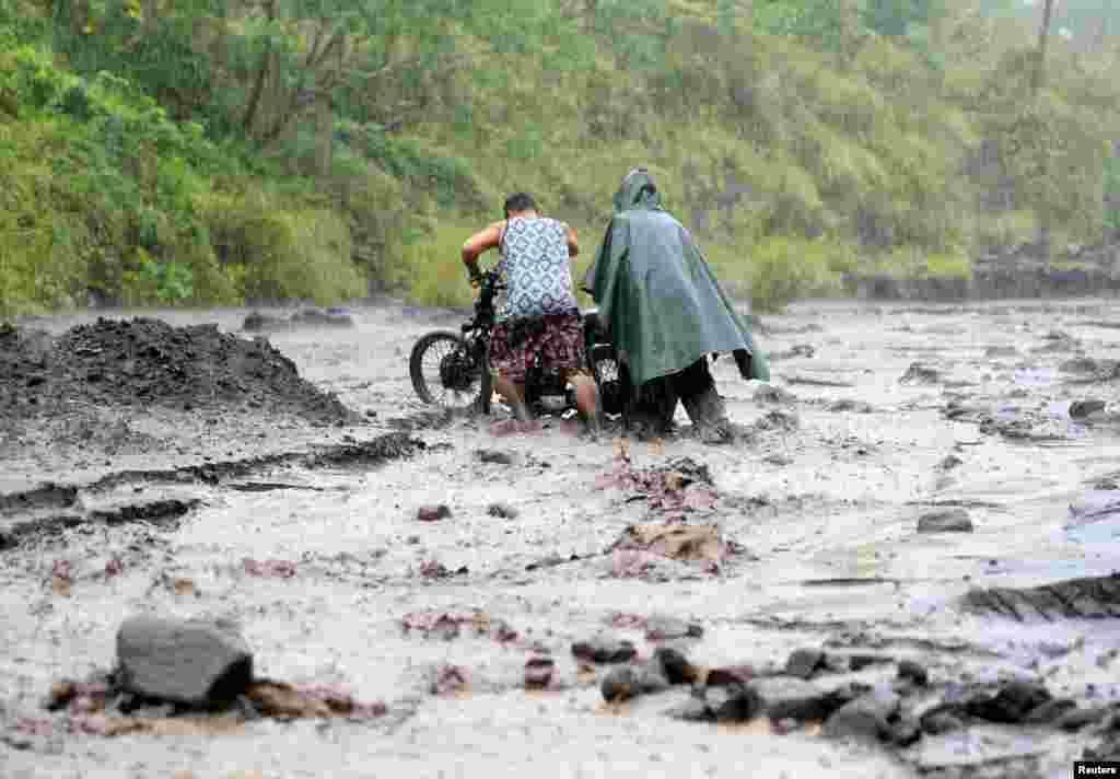 عبور ساکنان جنوب مانیل فیلیپین از رودخانه ای که گدازه های ناشی از فوران آتشفشان به درون آن سرازیر شده است