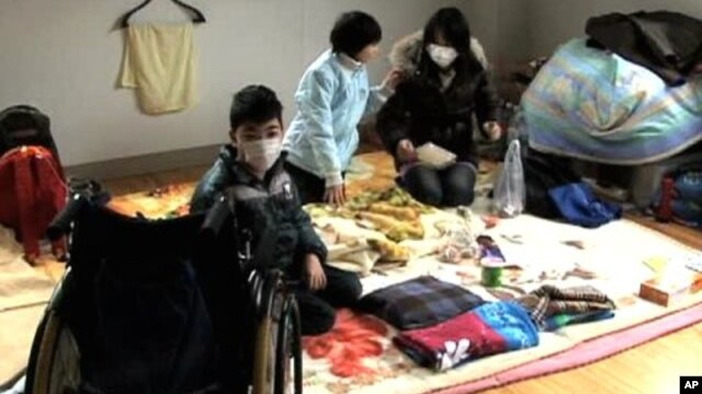 Mugen Takahashi, 11, with his sister and mother.  Despite being in a wheelchair, Mugen managed to escape the tsunami.