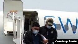 Edgardo Martinez-Cuellar, desciende escoltado del avión en que fue deportado a El Salvador el viernes (1 de mayo de 2020), para afrontar cargos de homicidio y terrorismo.
