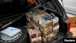 FILE - Money is seen piled in the back of a car in the Democratic Republic of Congo's capital Kinshasa.