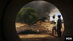 Para pekerja mengamati jaringan pipa minyak di Delta Niger yang terbakar akibat serangan para militan.