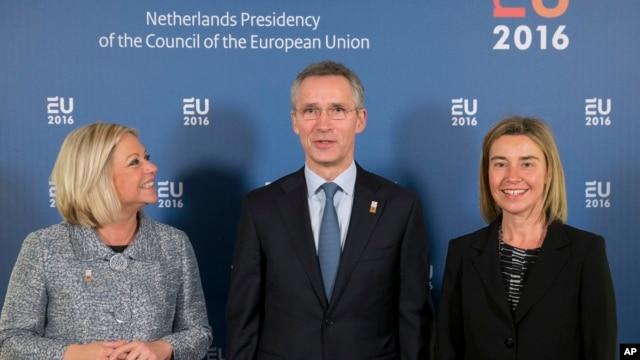 NATO Secretary General Jens Stoltenberg, center, is flanked by EU High Representative Federica Mogherini, right, and Netherlands' Defense Minister Jeanine Hennis-Plasschaert in Amsterdam, Netherlands, Feb. 5, 2016.
