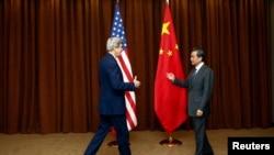 Menteri Luar Negeri China Wang Yi (kanan) menyambut Menteri Luar Negeri AS John Kerry dalam kunjungan di Beijing (14/2). (Reuters/Diego Azubel)