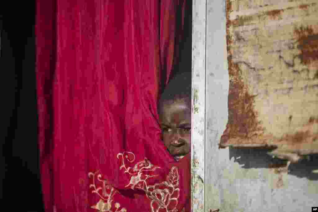 Jonelson Princeton, 7, who survived cholera as a newborn, peers out from inside his home which was once used as an office, on a former UN base where he lives with his parents and grandmother in Mirebalais, Haiti, Monday, Oct. 19, 2020. Ten years after a c