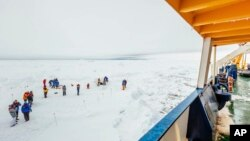 People gather on the ice next the Russian ship MV Akademik Shokalskiy that is trapped in thick Antarctic ice 1,500 nautical miles south of Hobart, Australia, Dec. 27, 2013.