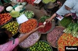 Seorang penjual sayuran mengambil uang dari pembelinya di sebuah pasar di Jakarta, 2 Juni 2017. Bank Indonesia memperkirakan inflasi 2019 akan berkisar 3,5 persen.