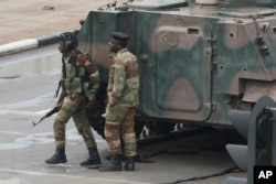 Armed soldiers stand by an armored vehicle on the road leading to President Robert Mugabe's office in Harare, Zimbabwe, Nov. 15, 2017.