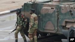 FILE: Armed soldiers stand by an armored vehicle on the road leading to President Robert Mugabe's office in Harare, Zimbabwe, Nov. 15, 2017.