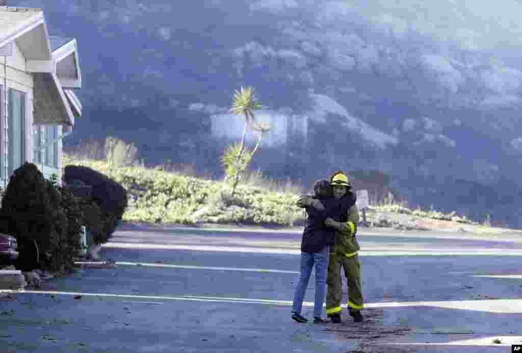 Жінка обіймає пожежника Саймона Гарсію. Вона повернулася та побачила, що її будинок не постраждав. Фоллбрук, штат Каліфорнія, 8 грудня 207 року.