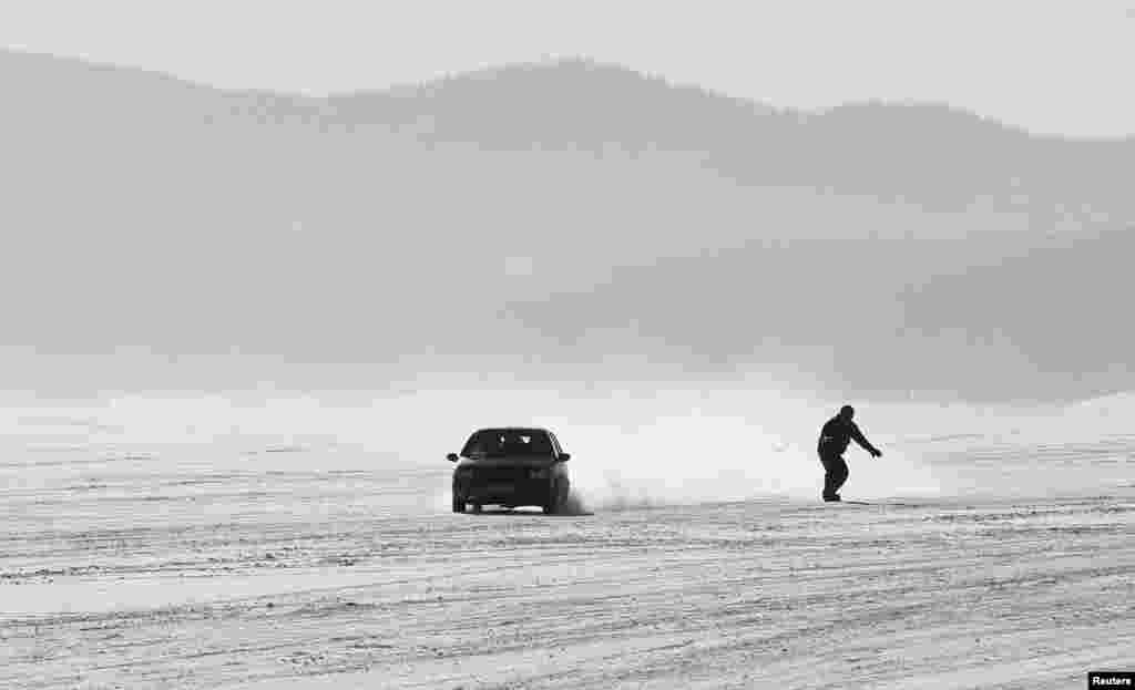 A car tows a snowboarder along the frozen surface of the Yenisei River in Taiga district, with the air temperature at about - 25° C (-13° F), outside Krasnoyarsk, Siberia, Russia.