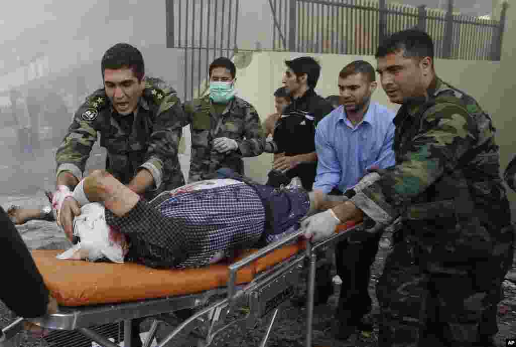 Lebanese army soldiers help an injured man after two explosions near the Iranian embassy in Beirut, Nov. 19, 2013.