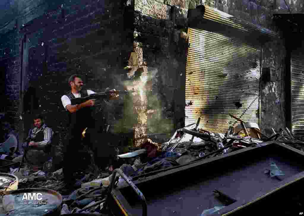 This citizen journalism image provided by Aleppo Media Center AMC shows a rebel firing his weapon during heavy clashes with soldiers in Aleppo, Syria, June 24, 2013.