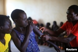 A South Sudan refugee girl is immunized and screened by a UNICEF health team at the U.N. managed refugees reception point at Elegu, within Amuru district of the northern region near the South Sudan-Uganda border, Aug. 21, 2016, before being transported to the Bidi Bidi refugee camp.