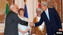 Menteri Luar Negeri AS John Kerry bersalaman dengan Menteri Luar Negeri Iran Mohammad Javad Zarif, disaksikan Menteri Luar Negeri Oman Yussef bin Alawi dan pemimpin kebijakan luar negeri Uni Eropa, Catherine Ashton (10/11), dalam pertemuan di Muscat.